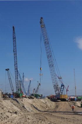 Dat de werkruimte krap is illustreert deze foto. Talloze machines doen op een betrekkelijk klein oppervlak hun werk. Dagelijks werken 400 à 500 mensen aan de bouw van de zeesluis, 24 uur per dag en zeven dagen in de week. (Foto: Ko van Leeuwen)