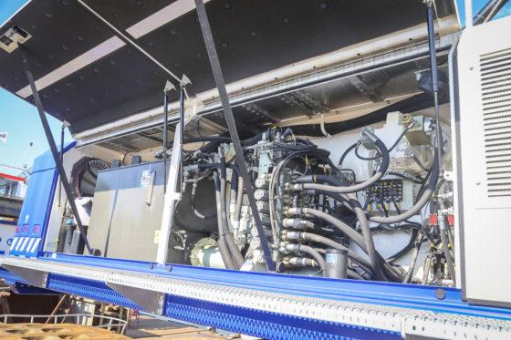 Aan de rechterzijde is het ventielenblok te vinden. Alle slangen en kabels zijn gecodeerd, wat handig is voor de monteur. Tevens hier te vinden zijn de AdBluetank, brandstoftank met vulpomp en op de voorgrond de hydrauliektank afgevuld met bio-olie.