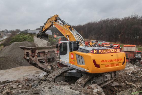 Grote schollen beton verdwijnen in de breker. Die Van der Heijden zelf bouwde.