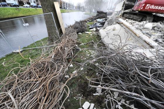 Om te voorkomen dat puin in de aangrenzende vijver beland zijn dikke bossen ijzer, afkomstig uit het kantoorcomplex, als een barrière langs de rand van het water gelegd.